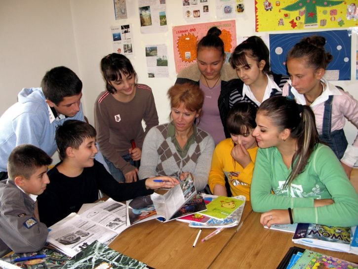 Female teacher sitting at table, surrounded by students